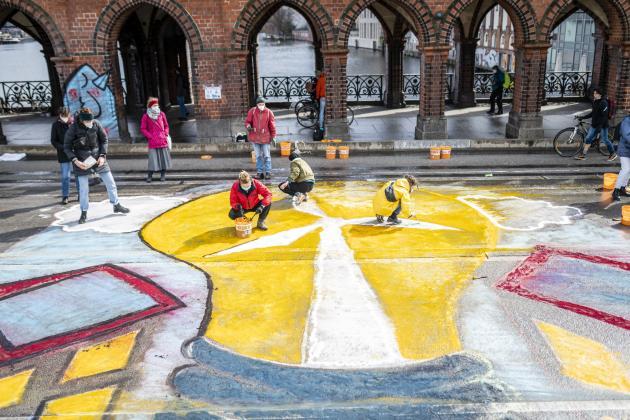 Jugendliche von Fridays for Future malen ein Windkraftrad auf den Straßenbelag